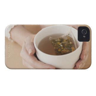 Mujer que sostiene la taza con té de manzanilla iPhone 4 cárcasa