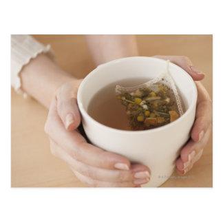 Mujer que sostiene la taza con té de manzanilla postal