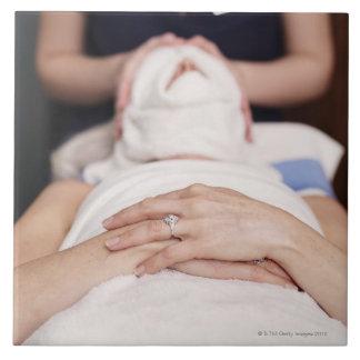 Mujer que tiene s [un tratamiento azulejo cuadrado grande