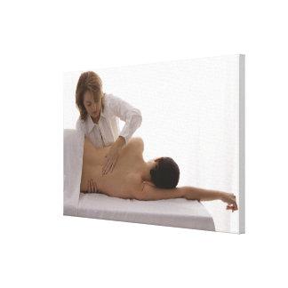 Mujer que tiene un masaje lona envuelta para galerías