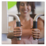 Mujer que usa la máquina del ejercicio en gimnasio azulejos ceramicos