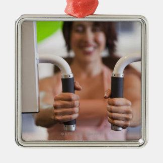 Mujer que usa la máquina del ejercicio en gimnasio adorno