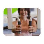Mujer que usa la máquina del ejercicio en gimnasio iman rectangular