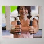 Mujer que usa la máquina del ejercicio en gimnasio impresiones