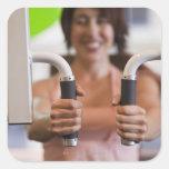 Mujer que usa la máquina del ejercicio en gimnasio calcomania cuadradas personalizada