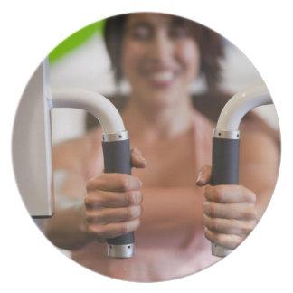 Mujer que usa la máquina del ejercicio en gimnasio platos