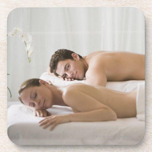 mujer y hombre que mienten en bancos del masaje posavasos de bebida