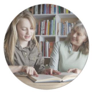 Mujer y nieta que leen junto platos