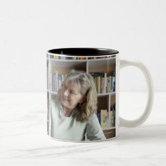 Mujer y nieta que leen junto taza de dos tonos