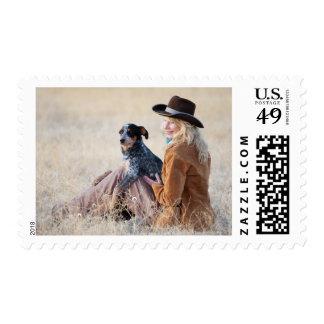 Mujer y perro que se sientan en campo estampillas