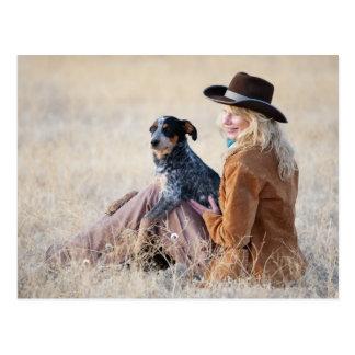 Mujer y perro que se sientan en campo tarjeta postal