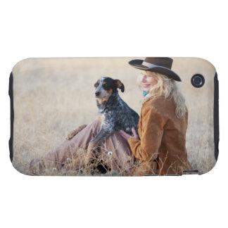 Mujer y perro que se sientan en campo tough iPhone 3 cárcasa