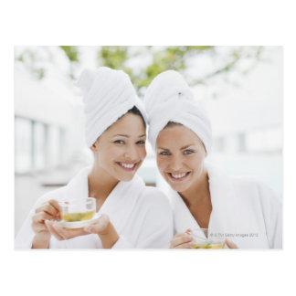 Mujeres en albornoces que beben té en el balneario postal