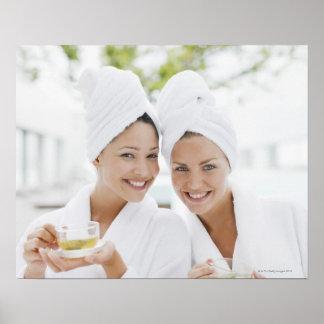 Mujeres en albornoces que beben té en el balneario póster