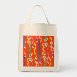 Multi-colored party streamers on a neon orange grocery tote bag