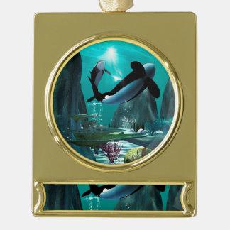 Mundo subacuático con las orcas que juegan adornos navideños dorados