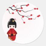 Muñeca de Kokeshi bajo rama de Sakura Etiquetas Redondas