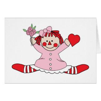 Muñeca de trapo linda que lleva a cabo un corazón tarjeta de felicitación