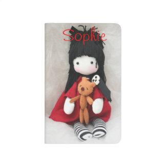 Muñeca gótica de la niña con el diario del bolsill cuaderno grapado