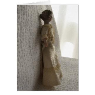 Muñeca miniatura en la tarjeta de nota de marfil