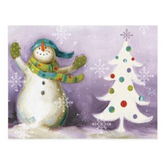 Muñeco de nieve con las manoplas y los árboles de postal