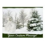 Muñeco de nieve con los árboles del invierno postal