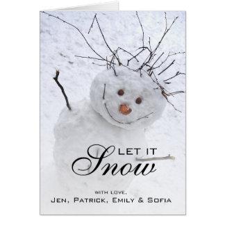 Muñeco de nieve del navidad que se sienta en un tarjeta de felicitación