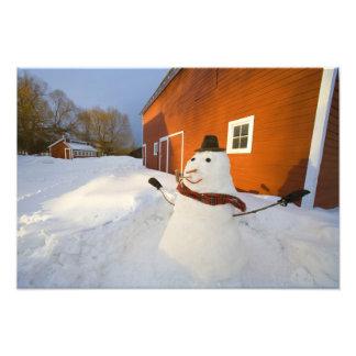 Muñeco de nieve delante del granero rojo en las ca fotografías