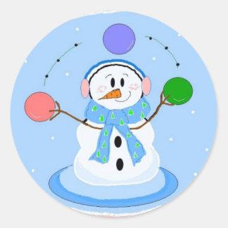 Muñeco de nieve que hace juegos malabares pegatina redonda