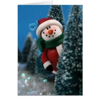 Muñeco de nieve que mira a escondidas detrás de un felicitacion