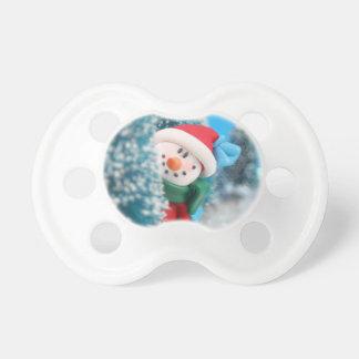 Muñeco de nieve que oculta o que mira a escondidas chupetes de bebé