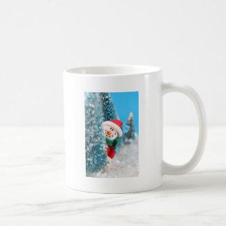 Muñeco de nieve que oculta o que mira a escondidas tazas de café