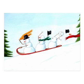 Muñecos de nieve en un trineo postales