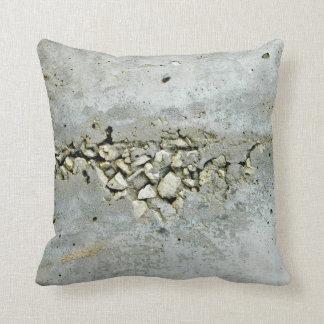 Muro de cemento agrietado con las pequeñas piedras cojin
