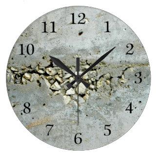Muro de cemento agrietado con las pequeñas piedras reloj redondo grande