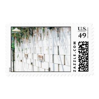Muro de cemento con las vides que cuelgan del top timbres postales