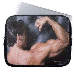 Muscular man flexing laptop computer sleeves