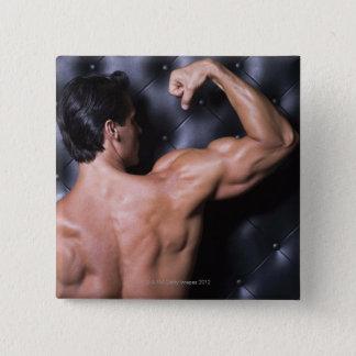 Muscular man flexing pinback button
