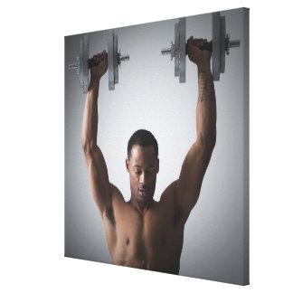 Muscular man lifting dumbbells 2 canvas print