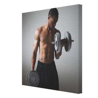 Muscular man lifting dumbbells canvas print