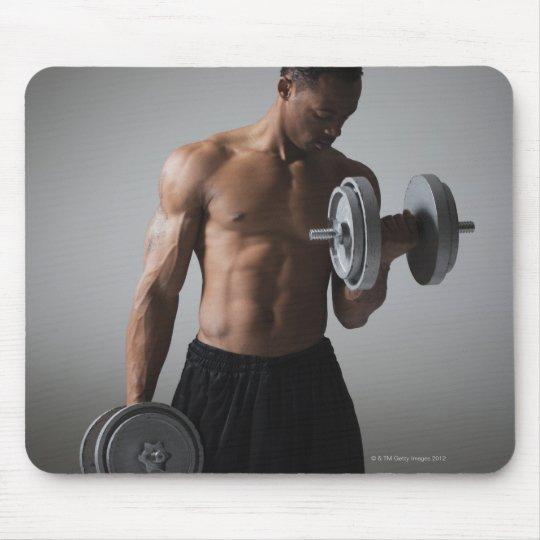 Muscular man lifting dumbbells mouse pad