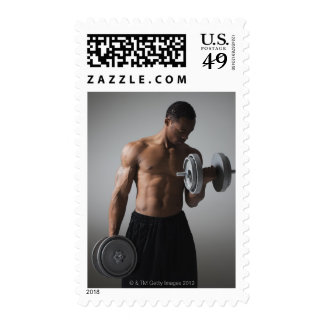 Muscular man lifting dumbbells postage stamp