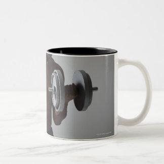 Muscular man lifting dumbbells Two-Tone coffee mug