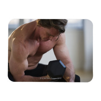 Muscular man lifting free weight magnet