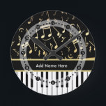 """Musical Notes and Piano Keys Black and Gold Round Clock<br><div class=""""desc"""">An elegant design for the pianist or keyboard player - featuring keyboard keys with golden colored musical notes on a black background. The background color can be changed to any color to suit your own needs and style, Customize the text on the golden colored strip between the piano keys and...</div>"""