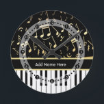 "Musical Notes and Piano Keys Black and Gold Round Clock<br><div class=""desc"">An elegant design for the pianist or keyboard player - featuring keyboard keys with golden colored musical notes on a black background. The background color can be changed to any color to suit your own needs and style, Customize the text on the golden colored strip between the piano keys and...</div>"