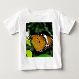Naranja, mariposa blanco y negro en la hoja playera para bebé