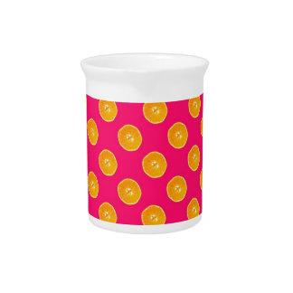 Naranjas con el fondo rosado jarras para bebida