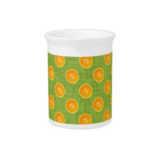 Naranjas con el fondo verde jarras para bebida