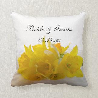 Narcisos amarillos en el boda blanco cojín